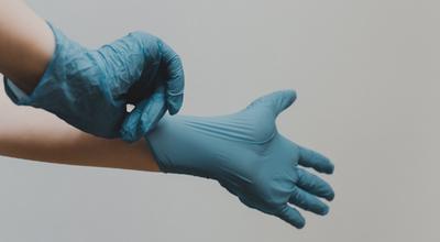 Imagen muestra las manos de profesinal de la salud colocándose guantes quirúrgicos